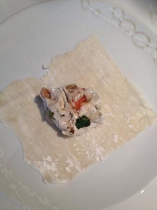 Sumerja las puntas de los dedos en el huevo y aplastar su pollo, verduras y filo en una bola áspera. Crear más plazas de la pasta filo y luego colocar su pelota blanda en el medio de los filo cuadrados.