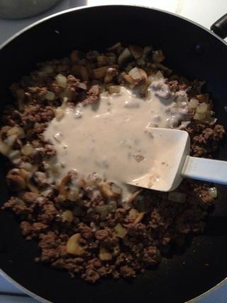 Cuando se realiza el último lote de setas, añadir de nuevo la carne de res, cebolla y otros hongos. A continuación, agregue una lata de crema de champiñones. Mezclar bien.