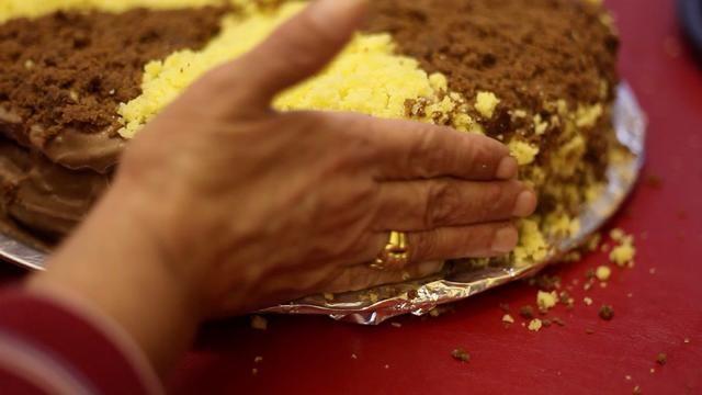Pulsar la mezcla de color de migas de alrededor del exterior de la torta.