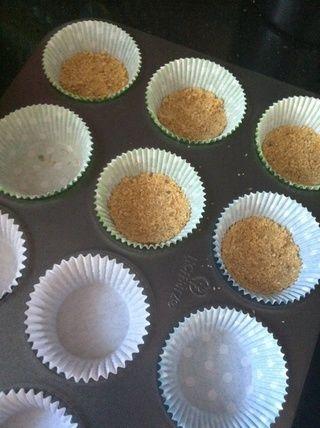Cuchara de manera uniforme entre sus latas magdalena alineados. Use una taza para comprimir sus galletas integrales para formar la corteza.