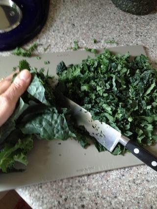 Rolle la kale juntos y picar finamente. Ver mi guía en hacer cruda ensalada de col blanca, sobre la forma de masajear la col rizada para que sea más fácil de digerir. (Frotar con sal corse y enjuague)