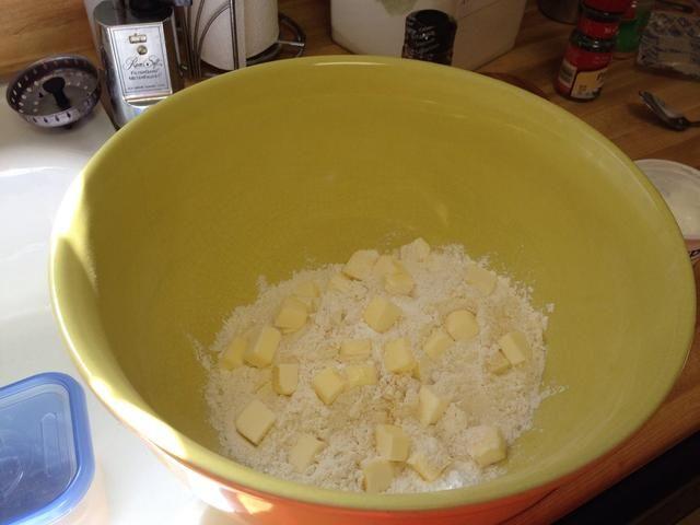Publique sus ajo en polvo de hornear y la sal. Remover. Caída en la mantequilla. Use un cortapastas o con los dedos para incorporar la mantequilla.