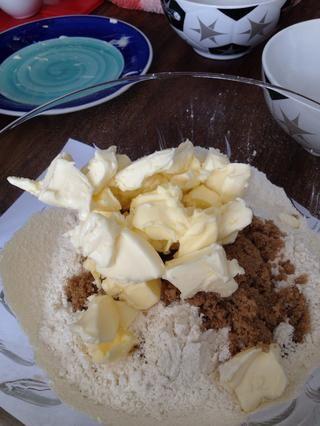 Mientras que el ruibarbo es cocinar, tomar la mantequilla fuera de la nevera y agregarlo a un recipiente con la harina tamizada y el azúcar marrón claro.