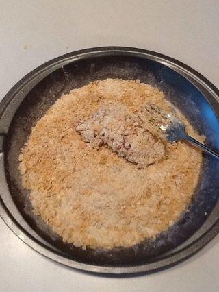 Da la vuelta al pollo con un tenedor y presione hacia abajo de nuevo. Scoop cereales alrededor de pollo si es necesario para cubrir uniformemente con la mezcla.