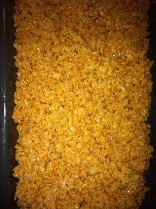 Y entonces usted saca la mezcla de cereales y ponerlo en la sartén y lo extendió el uso de papel de cera o una espátula con mantequilla y dejar que se enfríe durante al menos diez minutos o hasta endurecido