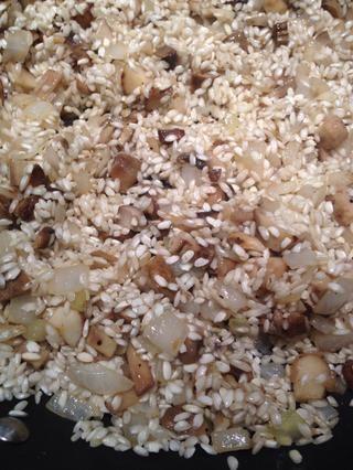 Revuelva para cubrir el arroz y se deja ir un par de minutos hasta que escuche algunos granos chisporrotea.
