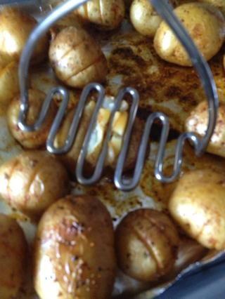 Cuando las patatas es lo suficientemente fría como para manejar, presione suavemente usando machacador de papas.
