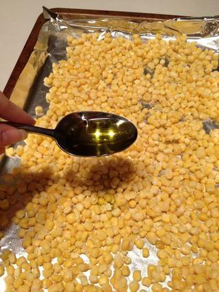 Rocíe el aceite de oliva sobre el maíz congelado. Usé unos 3 cucharadas luego suavemente moví el maíz, así que fue bien cubiertas.