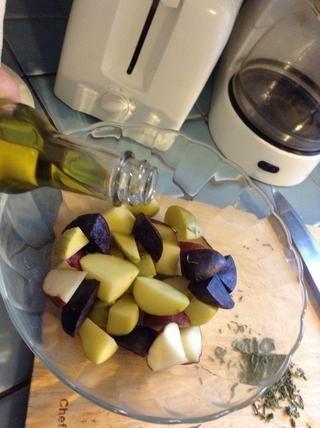 Rocíe las papas con aceite de oliva. Usted quiere lo suficiente para cubrir todas las patatas también.
