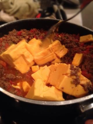 Añadir en las latas de Rotel, dejar cocer durante unos 5 min. , A continuación, agregue los cubos de queso.