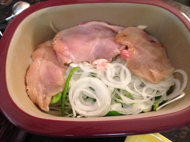 Coloque el lado de la cara de pollo sazonado en el panadero en la parte superior del pimiento y cebolla.