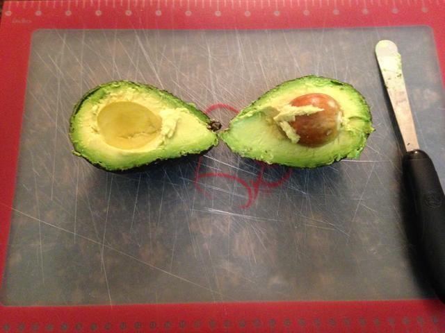 Usando Aguacate Peeler (o cuchillo de mantequilla) cortar todo el camino alrededor del aguacate hasta obtener dos partes. Como se ve aquí.