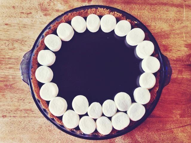 Con unas tijeras de cocina o un cuchillo, corte malvaviscos en medio. Colocar los malvaviscos en círculos concéntricos en el pastel hasta que esté cubierto.