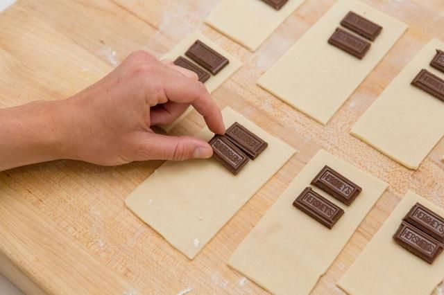 Coloque de dos Hershey's chocolate pieces onto each crust rectangle.