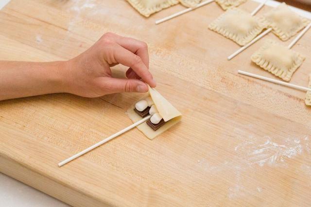 Coloque un palo piruleta entre las dos piezas de chocolate sobre la mitad del rectángulo de corteza y presione ligeramente hacia abajo. Luego, doblar sobre la otra mitad de su pieza de corteza.