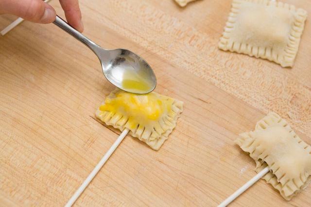 Batir el huevo. Cepillo parte superior de los estallidos con la mezcla de huevo. Se le da un bonito color marrón de oro cuando se trata de salir del horno.