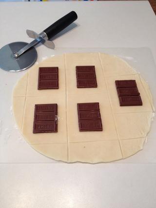 Coloque las barras de chocolate en la corteza de pastel y cortar rectángulos alrededor del chocolate, dejando espacio a lo largo del perímetro.