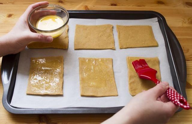 Estirar segundo rectángulo en las mismas dimensiones que la primera, cortado en 6 rectángulos. Batir el agua y el huevo en un tazón pequeño y cepillar una capa fina sobre rectángulos refrigerados.