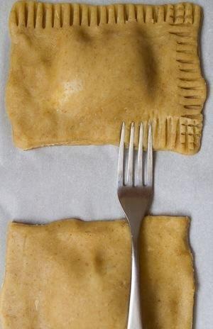 Coloque un rectángulo nonchilled sobre la crema de malvaviscos. Presione sobre los bordes para pegar los 2 juntos, presione ligeramente en cimas de tarta de pop para aplanar. Sumerja un tenedor en la harina y luego doble los bordes de la tarta.