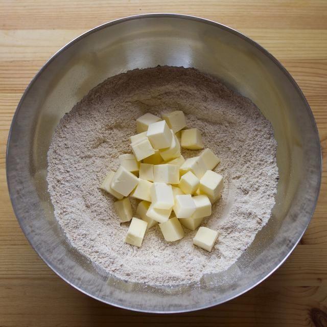 Poner la mantequilla en cubos en la mezcla y mezclar con los dedos para cubrir todos los lados de la mantequilla.