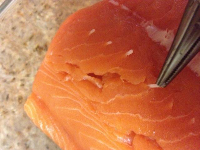 Prepara el salmón si es necesario: pinzas de punta de aguja funcionan bien para quitar los huesos, deje la piel en