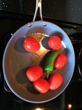 Rocíe una sartén con aceite en aerosol. Colocar en fuego medio-alto y agregue los tomates y el jalapeño. usted'll want to cook each side until they're charred.