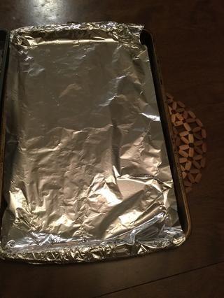 Línea de otra bandeja de horno con papel de aluminio, engrasar con Pam