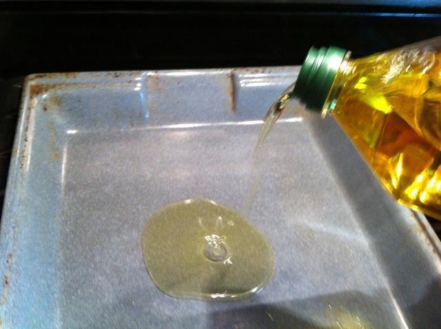Añadir el aceite a una asadera. Cubra completamente abajo.