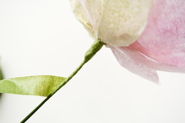 Envuelva la cinta alrededor del alambre y pétalos adicionales hasta que esté satisfecho con la plenitud de su flor. Continúe envolviendo la cinta por el cable unas pocas pulgadas para mantenerlo seguro.