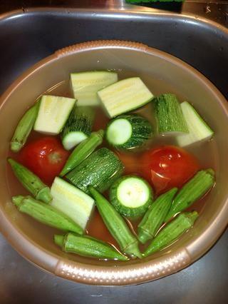 Enjuague el arroz hasta que el agua salga limpia. Ponga el agua fresca en el cuenco con el arroz. Lavar y preparar las verduras. Póngalos en el cuenco con el arroz y el agua.