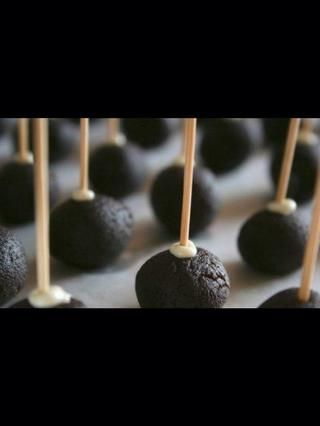 Sumerja palos polo en el chocolate derretido y empujarlos a las bolas de la torta. Enfríe en el refrigerador hasta que el chocolate se endurezca