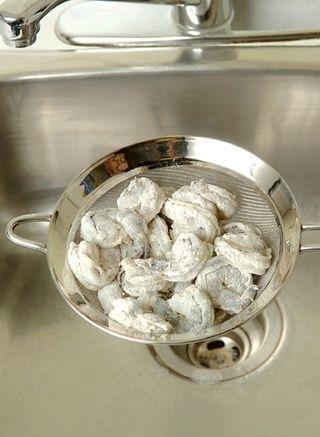 Coloque los camarones harina en un colador de malla media, bien celebrada sobre el fregadero. Agitar el colador para eliminar cualquier exceso de harina desde el camarón. Dejar de lado.