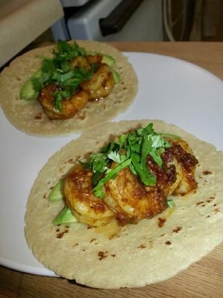 En una tortilla caliente, agregar los camarones y cilantro rodajas de aguacate, sazonado con guarnición.
