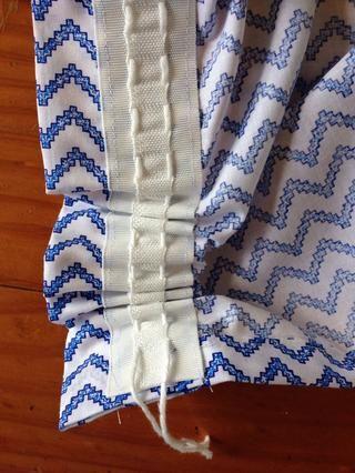 Tire de las dos cadenas en los extremos de la cinta y recoger la tela.