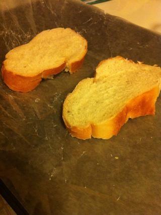 Cortar el pan en rodajas y colocar sobre papel de cera o un molde para pizza