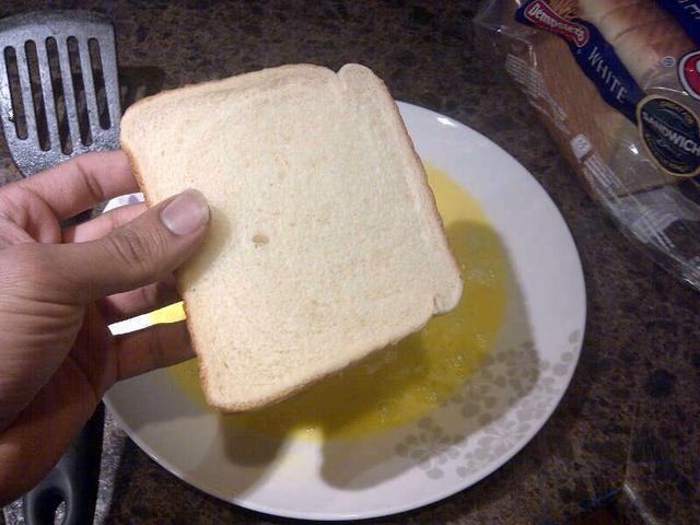 Tome su pan y moja ambos lados en los huevos