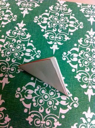 Dobla el nuevo cuadrado por la mitad en diagonal. Ahora usted tiene un triángulo rectángulo con dos ángulos de 45 grados. El más cercano a la esquina inferior derecha en esta foto es la que va a mantener durante el corte.