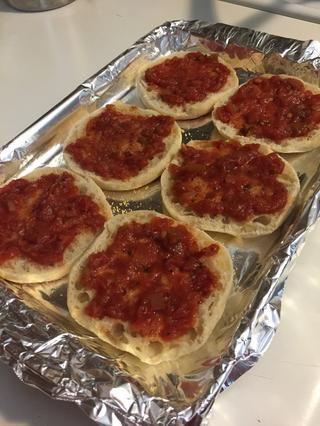 Cubra los panecillos ingleses con su salsa de pizza favorita o salsa de tomate.