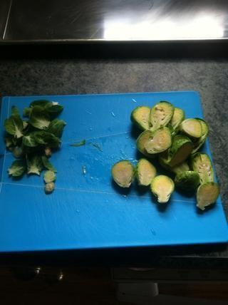 Coge tu tabla de cortar y cuchillo y picar los extremos desagradables fuera de los brotes. Proceda a cortar los brotes a lo largo, por la mitad.