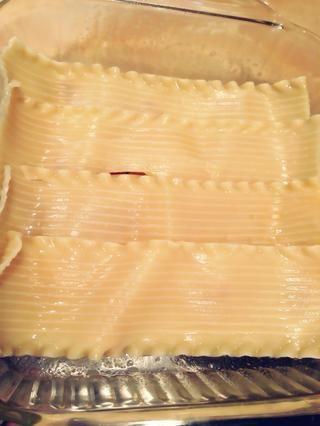 Engrase un molde 9x14 también. Comience por capas de fideos en el fondo de la sartén, un poco por encima. Los fideos pueden no ser suficiente para que el pan, por lo que un fideo pueden necesitar ser cortado a la medida.