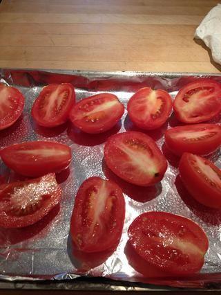 Rocíe una bandeja forrada con papel de aceite de oliva. Coloque los tomates cortados por la mitad. Espolvorear uniformemente con sal y pimienta al gusto. Añadir el azúcar, el romero y el ajo. Rocíe con aceite de oliva.