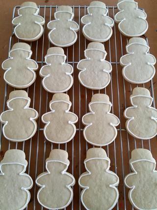Hornee muñecos de nieve en papel pergamino 375 grados durante 8-10 minutos. Dejar enfriar. Tome un muñeco de nieve sólido (esta será la parte superior de la cookie) y delinear con formación de hielo real.