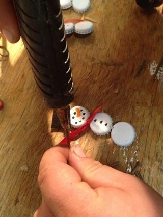 Cuando pegamento del brillo se seca por completo, utilice una pistola de pegamento caliente para pegar el sombrero de copa en nuestro muñeco de nieve's head. You want to make sure you don't cover the hole in the top bottle cap (for the ornament hook.)