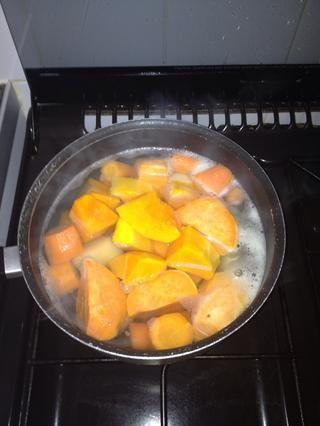 Retire con cuidado y cortar las patatas, las zanahorias y butternut squash y colocarlos en el agua hirviendo. Mantener a fuego medio.