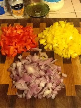 Picar la cebolla morada, pimiento amarillo y pimiento rojo.