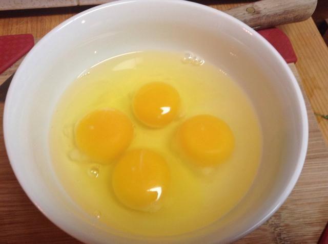 Grieta 4 huevos en un bol.