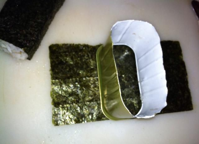 Coloque el musubi-moho en el centro del nori. (Si no't have a musubi-mold, you can do what I did and make a ghetto mold by cutting out the closed end of the Spam can... ahahaha)