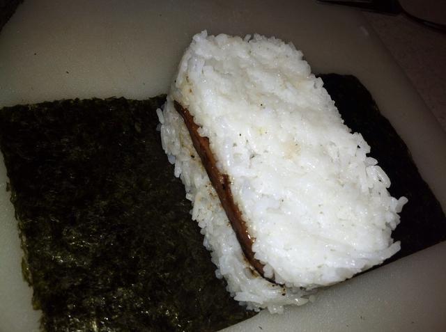 Utilice una cuchara (o su mango musubi), presione hacia abajo en el arroz y utilice la otra mano para tirar el molde y liberar el musubi.