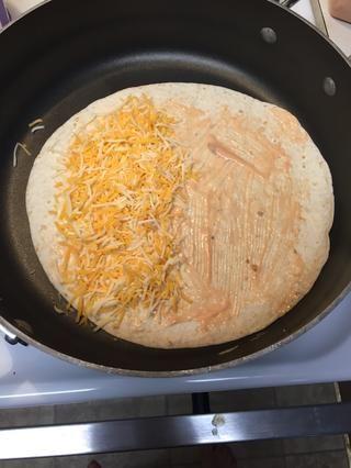 Difunde tu cantidad deseada de queso en la mitad de la tortilla.
