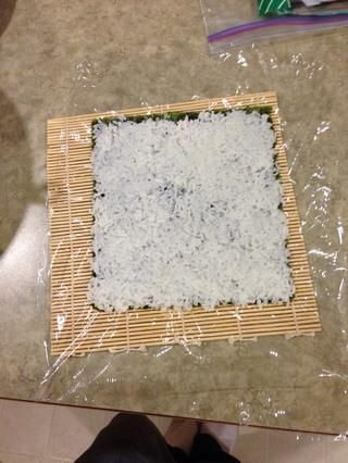 Coloque el arroz fino en algas secas y darle la vuelta a una envoltura de plástico